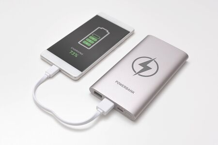 USB charger plugged in to smart phone. Power bank, mobile phone battery on desk concept