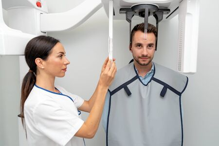 Handsome man patient standing in x-ray machine. Panoramic radiography at professional dental clinic.