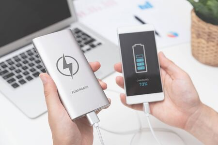 Man connecting USB charger to smart phone. Power bank, mobile phone battery on desk concept 写真素材