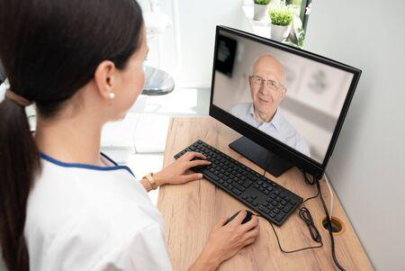 Arts en senior man patiënt medisch consult, telehealth, telemedicine, concept voor gezondheidszorg op afstand. Stockfoto