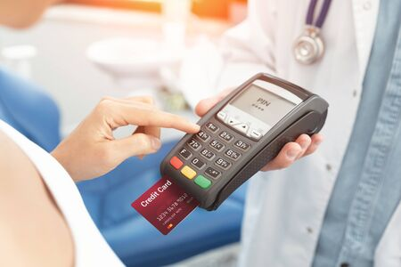 Doctor is holding payment terminal in hands. Paying for health care. 写真素材