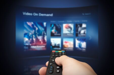 VOD service screen with remote control in hand. Video On Demand television internet stream multimedia concept 写真素材