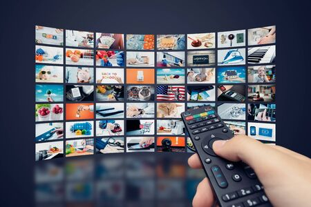 Multimedia video wall television broadcast. Hand holding remote control.