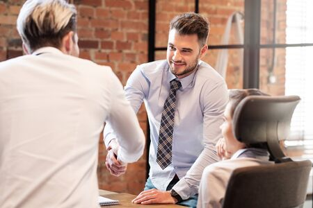 Men shaking hands while working in team. Business contract or agreement sign concept