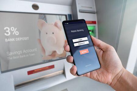 신용 카드를 사용하지 않고 ATM에서 돈을 인출하십시오. 모바일 뱅킹 로그인 화면이있는 휴대 전화를 들고있는 사람. 스톡 콘텐츠