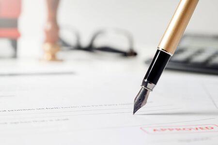 Notar unterzeichnet rechtsgültigen Vertrag. Nahaufnahme von Füllfederhalter auf Papier Standard-Bild