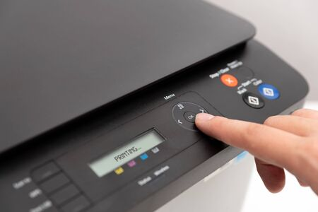 Hand pressing button on panel of printer. Multifunction device, printer, copier. Stock Photo