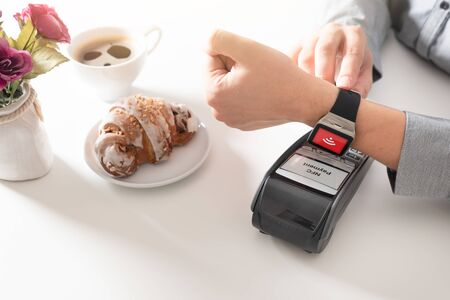 Man using smart watch to pay in restaurant. NFC contactless convenient payment service
