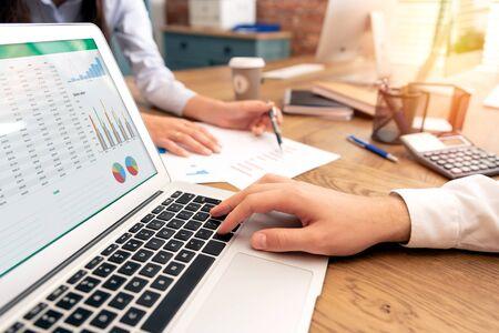 Inwestorzy pracują w biurze. Doradca finansowy z laptopem i wykresem na ekranie. Kobieta wskazująca na oświadczenie