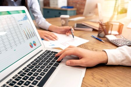 Los inversores trabajan en la oficina. Asesor financiero con laptop y gráfico en pantalla. Mujer señalando declaración