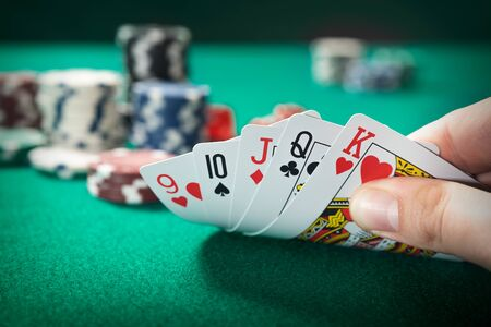 Man plays poker in the casino. Holding cards in hand, gambling concept