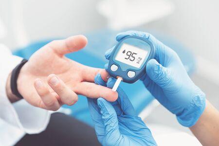 Arts die de bloedsuikerspiegel controleert met glucometer. Behandeling van diabetesconcept. Stockfoto