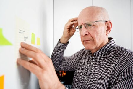 Elderly man looking at notes. Forgetful senior with dementia, memory problem, health concept Banque d'images