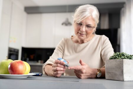 Senior woman checking her blood glucose level. Health care diabetes concept Stock Photo
