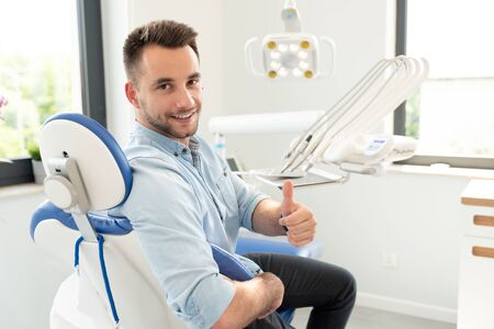 Handsome man showing thumbs up and smiling sitting at the dental chair. Professional dental clinic, healthy teeth concept. Archivio Fotografico