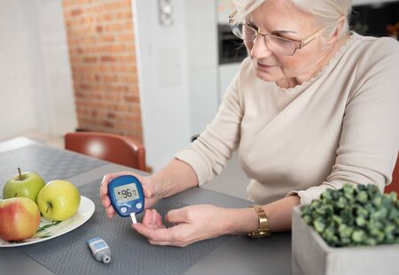 Senior woman with glucometer checking blood sugar level at home. Diabetes, health care concept Stock Photo
