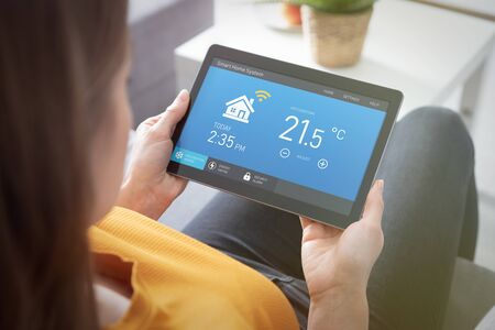 Woman using smart home application on tablet. Smart home system concept