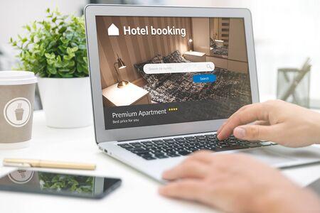 El hombre hace reservas de hotel a través de Internet. Turismo, concepto de vacaciones