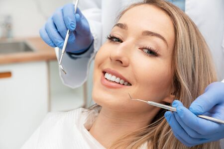 Woman having teeth examined at dentists. Teeth whitening, dental care concept