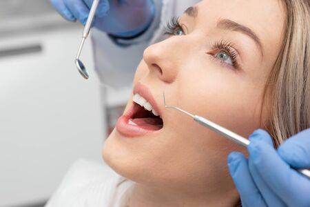 Woman having teeth examined at dentists. Teeth whitening, dental care concept Banco de Imagens