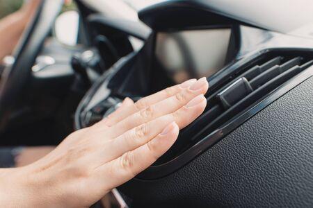 Car air conditioning. Woman checks air conditioning in a car 版權商用圖片