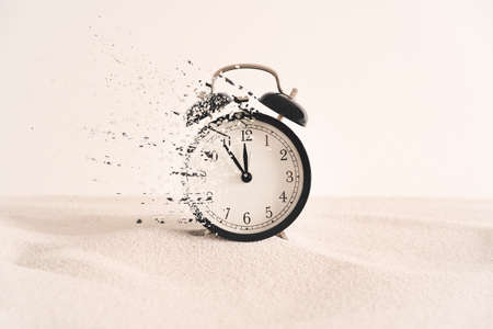 Concept of passing away, the clock breaks down into pieces. Analog clock in the sand, with dispersion effect.