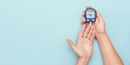 Man using glucometer, checking blood sugar level. Wide image with copy space, blue background. Diabetes concept