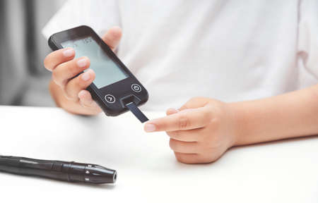 Young boy using glucometer, checking blood sugar level. Diabetes and children health care concept