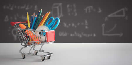 Back to school, student stuff in shopping trolley, board in background