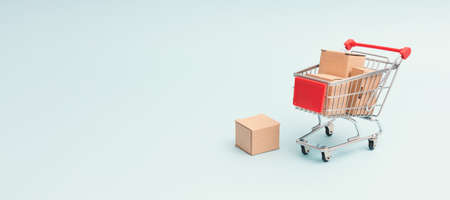 Shopping cart with cardboard boxes. Internet commerce concept, banner background with copy space
