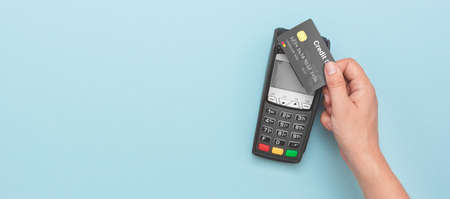 Credit card payment terminal. Man using credit card. Wide image with copy space and blue background