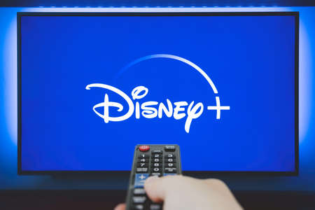 Wroclaw, Poland - OCT 13, 2020: Man holds a remote control. Disney + logo on TV screen in background. Disney + is a new online video streaming service