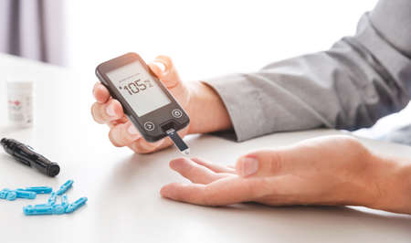 Man using glucometer, checking blood sugar level. Diabetes concept