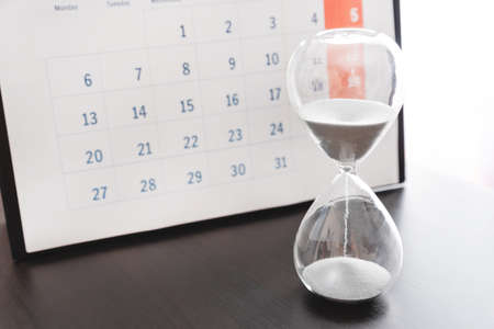 Time passing concept, time slipping away. Hourglass and the calendar Stockfoto
