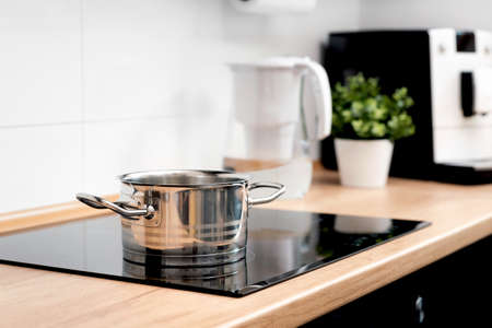 Pot in the kitchen on the induction hob. Induction electrical stove Foto de archivo