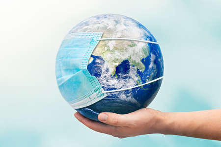 Hand holding Earth globe with face mask. World pandemic concept.