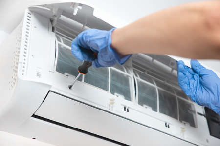 Modern air conditioner unit service. Cleaning the filter, fumigation. Air conditioner service.