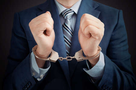 Businessman arrested for corruption. Man in a suit with handcuffs on his hands