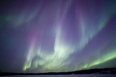 Northern lights aurora borealis in the night sky over beautiful frozen lake landscape Stock Photo