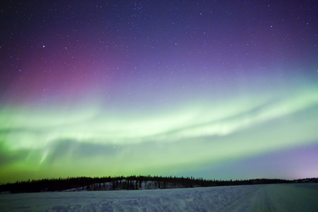 Northern lights aurora borealis in the night sky over beautiful frozen lake landscape Stok Fotoğraf