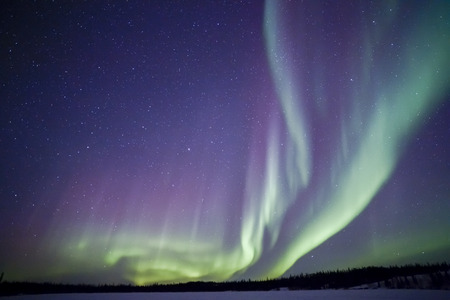 Northern lights aurora borealis in the night sky over beautiful frozen lake landscape Archivio Fotografico