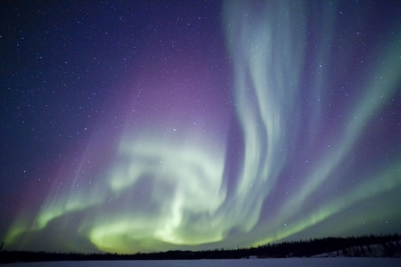 Northern lights aurora borealis in the night sky over beautiful frozen lake landscape Banque d'images