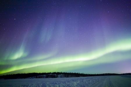 Northern lights aurora borealis in the night sky over beautiful frozen lake landscape Standard-Bild