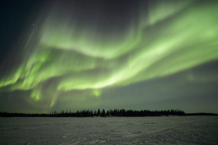 Northern lights aurora borealis in the night sky over beautiful frozen lake landscape photo