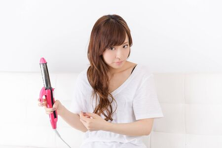 curling irons: Young Japanese woman to set the hair Stock Photo
