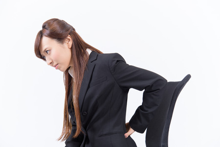 Young Japanese business woman has a bad lower back on white background Stok Fotoğraf