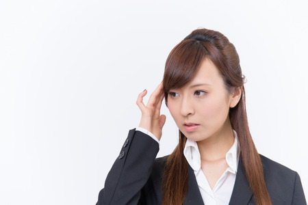 woman posing: Japanese young woman with a headache holding head, isolated on white background