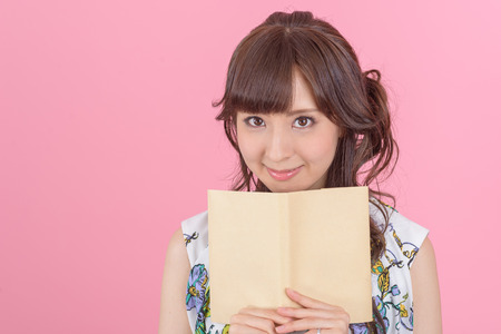 essays: happy young japanese woman reading storybook on couch at home