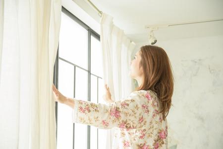 Een mooie Japanse vrouw om het gordijn bij het ontwaken openen Stockfoto