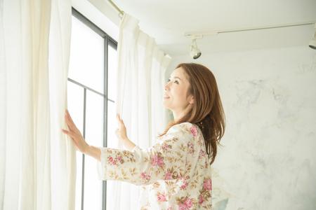 깨어날 때 커튼을 여는 아름다운 일본 여성 1 명